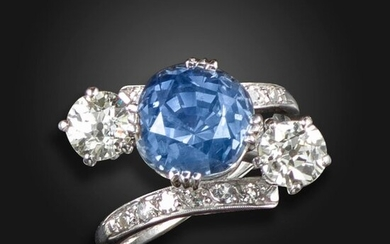 A sapphire and diamond three-stone ring, the cushion-shaped sapphire weighs 6.81cts, with an old circular-cut diamond to each shoulder, with further single-cut diamonds to the crossover mount in white gold, size I Accompanied by report number 18427...