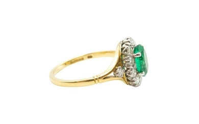 AN EMERALD AND DIAMOND CLUSTER RING Centrally-set with