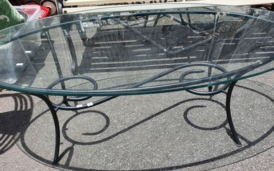 AN OVAL GLASS TOP WROUGHT IRON BASED COFFEE TABLE