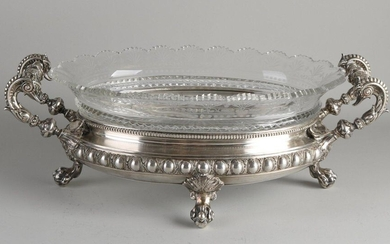 Beautiful silver display bowl, 800/000, oval model with cut crystal inner bowl with fan cut and etched finish. Placed in a silver holder on 4 claw feet, with medallions and pearl rim. The handles are made of curly swan heads with acanthus leaves...