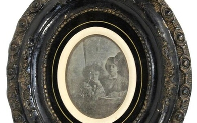 [DAGUERREOTYPE]. Two young children in schoolgirls in school coats, crouched down. circa 1860. Size of subject ovalized 9 x 7.2 cm. Beautiful blackened wood frame decorated with flowers and fruits. Period name and date in black ink on the back.
