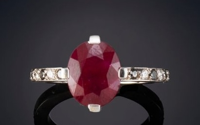 RING WITH AN OVAL-SIZE RUBY FLANKED BY BLACK...