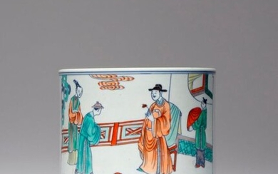 A CHINESE DOUCAI BRUSHPOT, BITONG KANGXI 1662-1722 The cylindrical body decorated with two large rectangular panels enclosing figural scenes, one depicting a scholar holding a lotus flower as he greets a gentleman and a beauty, with his attendant...