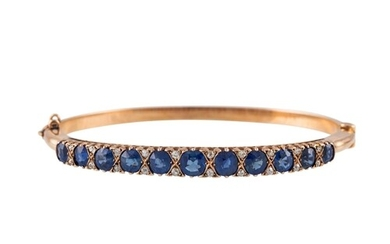 A DIAMOND AND SAPPHIRE BANGLE, the oval sapphires set betwee...