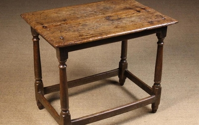 A Late 17th/Early 18th Century Centre Table. The planked top with bevelled ends standing on turned c