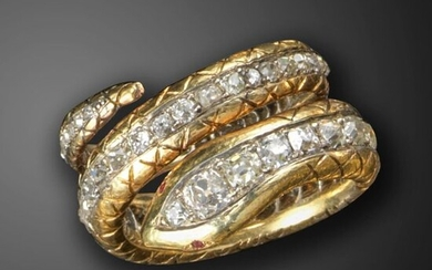 A diamond-set snake ring, the coiled snake body set with a line of graduated old cushion-shaped diamonds, with ruby eyes and engraved decoration to the body in two-colour gold, size N approximately
