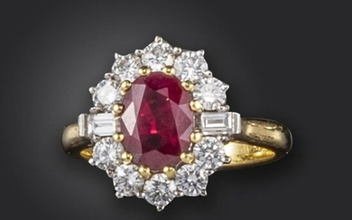 A ruby and diamond cluster ring, the oval-shaped ruby set within a surround of circular-cut and baguette-shaped diamonds in 18ct gold, London hallmarks for 1999, size N 1/2
