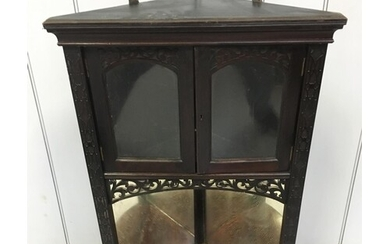 A small, ebonized hanging corner cabinet. Cupboard above mir...