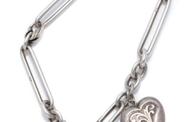 AN ANTIQUE SILVER PADLOCK BRACELET; fetter and fancy link attached with a silver front and back heart shape locket charm to an heart...