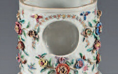 Chinese porcelain watch holder. 18th century. Contoured oval shape applied with garlands of flowers in relief and resting on a gadrooned base, decorated with enamels of the Rose