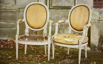 Pair of cabriolet armchairs with medallion backrest in white lacquered wood, the armrests decorated with oak leaves, foliage, flowers and roughened fluting, roughened fluted feet (accidents and upholstery to be redone).