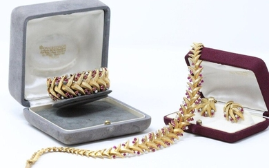 Set in 18k (750) yellow gold and platinum comprising a drop articulated necklace, a large articulated bracelet and a pair of ear clips decorated with interlacing foliage adorned with brilliants and small round faceted rubies.