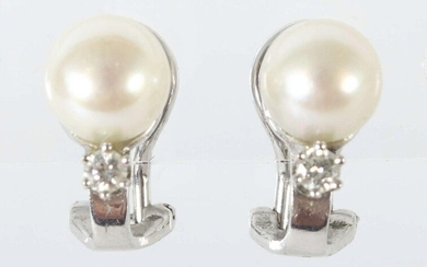 pair of earclips 1980/90's, white-gold 585, set with cultured pearl and one brilliant each (total approx. 0,1 ct), with hallmark of purity, total weight approx. 4,5 g, h: 1,5 cm. Slight signs of wear.