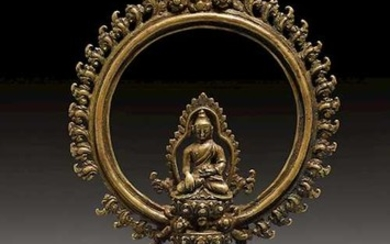 A BRONZE FITTING WITH BUDHA IN AN AUREOLE.