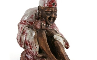 A Chinese Shiwan pottery figure in the form of an emaciated ...
