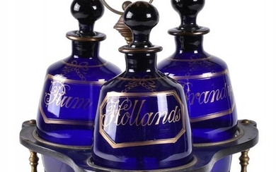 A Regency papier mâché tripartite decanter stand and three blue glass barrel-shaped decanters and stoppers