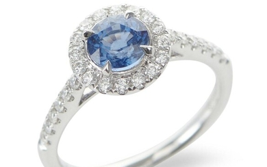 A SAPPHIRE AND DIAMOND CLUSTER RING IN 18CT WHITE GOLD, CENTRALLY SET WITH A ROUND CUT BLUE SAPPHIRE OF 1.20CTS, IN A SURROUND OF DI...