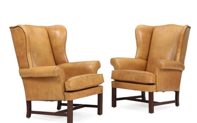 A pair of George III style library wing chairs, mahogany legs and upholstered with leather....