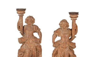 A pair of German or Austrian carved limewood figural candlesticks, 18th century