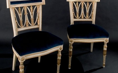 A pair of white lacquered and gilt wood chairs