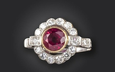 A ruby and diamond cluster ring, set with a circular-cut ruby within a surround of single-cut diamonds, with further diamonds to the shoulders in platinum and gold, size M