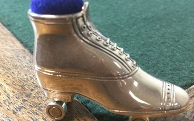 A silver pin cushion, in the form of a roller skate, stamped...