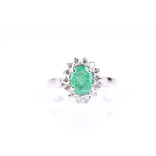 An emerald and diamond cluster ring, the oval cut emerald, i...