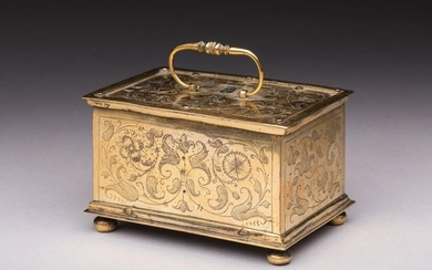 GOLDEN METAL BOX engraved with chiselled decoration of interlacing, foliage and floral motifs on all sides and visible screws, the upper part with movable handle. The interior reveals a complication mechanism. Four ball feet. Work in the tradition of...