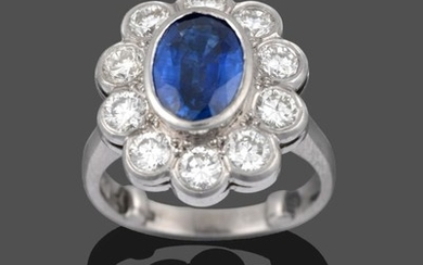 A Platinum Sapphire and Diamond Cluster Ring, the oval mixed...