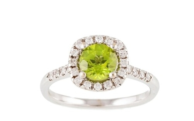A PERIDOT AND DIAMOND CLUSTER RING, mounted in white metal. ...