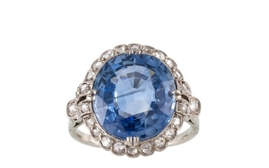 A SAPPHIRE AND DIAMOND CLUSTER RING, the large oval sapphire...