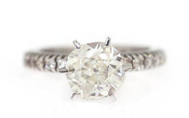 A diamond ring set with an old-mine cut diamond weighing app. 1.50 ct. flanked by...