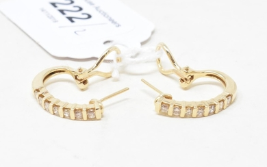 A pair of gold and diamond half hoop earrings