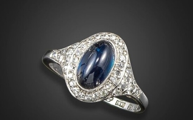 A sapphire and diamond cluster ring, the cabochon sapphire weighs 2.28cts and is set within a surround of old single-cut diamonds in white gold, size Q