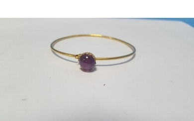 AN UNMARKED YELLOW METAL BANGLE SET WITH A PURPLE CABACHON P...