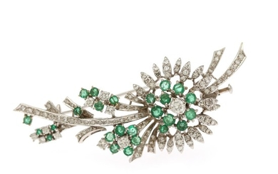An emerald and diamond brooch set with numerous circuluar-cut emeralds and numerous brilliant-cut and single-cut diamonds, mounted in 18k white gold.
