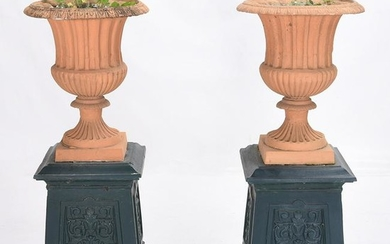 Pair of Outdoor Urns on Cast Iron Plinths.
