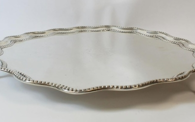Silver circular tray with wavy beaded and moulded edge on cl...