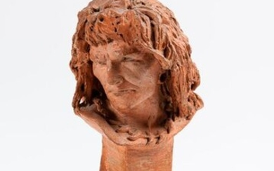 Terracotta man's head. It rests on a red marble pedestal (small accidents).