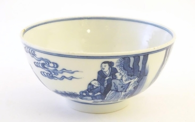 A Chinese blue and white bowl depicting scenes of figures in...