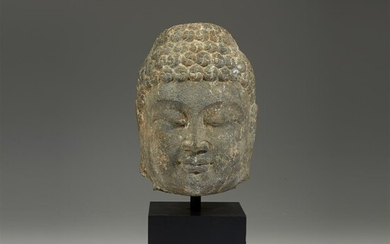 A Chinese carved grey stone head of a Buddha...