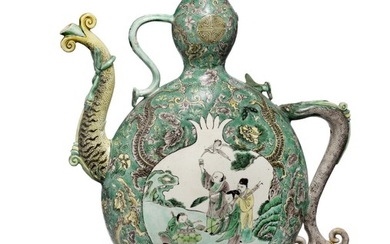 A Chinese famille verte enamel sur biscuit wine ewer decorated in colours the sides with pomegranate and peach cartouche. Qing, 18th century ? H. 30 cm.