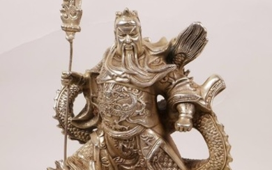 A Chinese silvered metal figure of a warrior deity standing ...