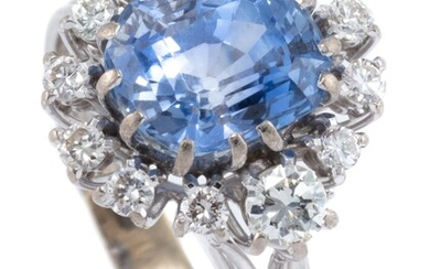 AN 18CT WHITE GOLD SAPPHIRE AND DIAMOND CLUSTER RING; centring an emerald cut fine blue Ceylon sapphire of approx. 5.50ct with 5 rou...