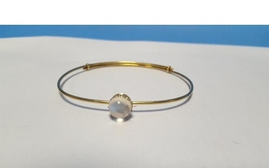 AN UNMARKED YELLOW METAL BANGLE SET WITH A MOONSTONE. Approx...