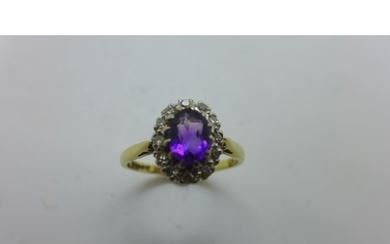 An 18ct gold amethyst and diamond cluster ring, the central ...