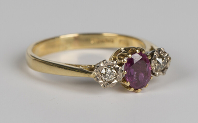 An 18ct gold, ruby and diamond ring, claw set with an oval cut ruby between two circular cut diamond