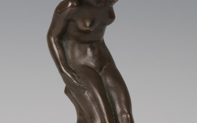 An early 20th century brown patinated cast bronze figure of a nude lady, leaning upon a rocky ledge