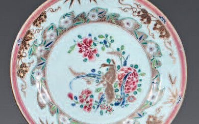 Chinese porcelain plate. Qianlong, 18th century. Decorated with enamels of the Rose Family, in the center of two roosters facing each other in a landscape in a medallion with a frieze of ironwork, the wing with bunches of flowers, gold filet on the...