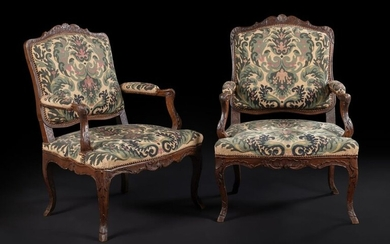 Pair of stained wood armchairs with flat backs decorated with shells, foliage and latticework, resting on curved legs.